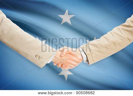 Businessmen Handshake With Flag On Background - Micronesia