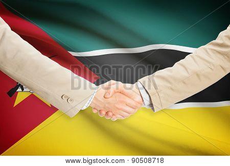 Businessmen Handshake With Flag On Background - Mozambique