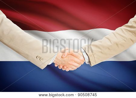 Businessmen Handshake With Flag On Background - Netherlands