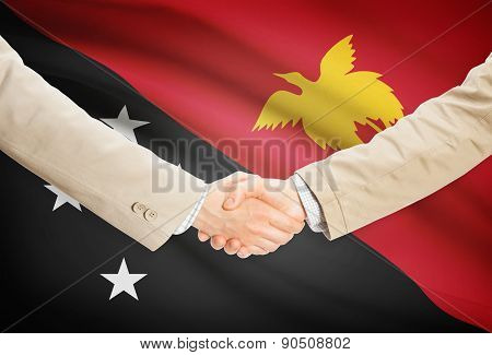 Businessmen Handshake With Flag On Background - Papua New Guinea