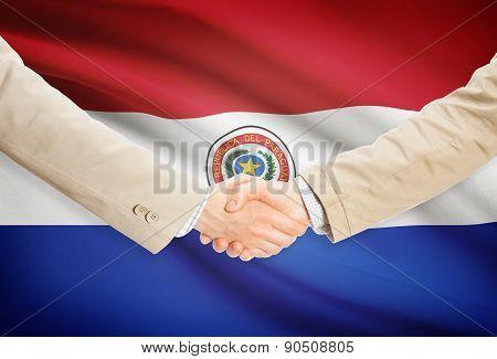 Businessmen Handshake With Flag On Background - Paraguay