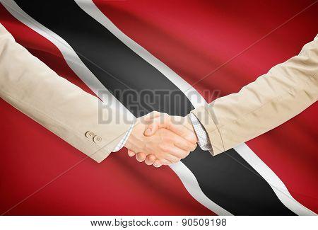Businessmen Handshake With Flag On Background - Trinidad And Tobago