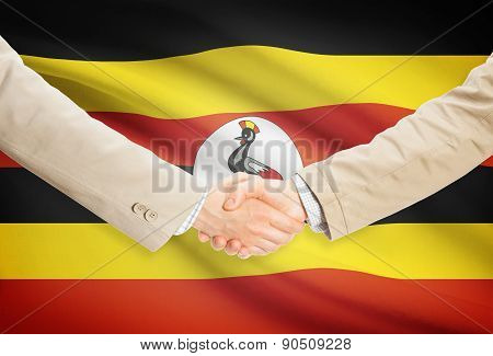 Businessmen Handshake With Flag On Background - Uganda