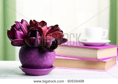 Beautiful tulips in pot with books on fabric background