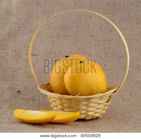 Mango fruit in basket on sack cloth
