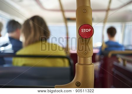 Detail of red stop button inside double decker bus in London, UK, with passengers seated in the blurred background.