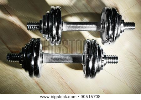 Dumbbells on wooden floor background