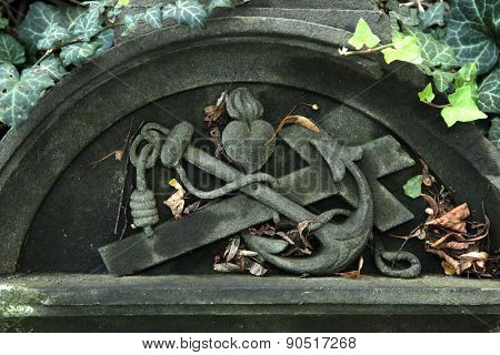Anchor, cross and heart depicted in the abandoned tombstone at the Malostransky Cemetery in Prague, Czech Republic.