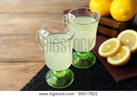 Still life with lemon juice and sliced lemons on wooden background
