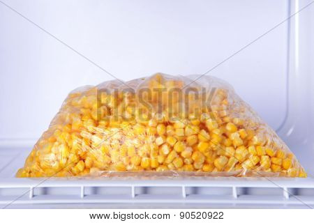 Frozen corn in bag in freezer close up