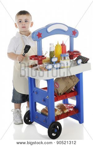 A young preschooler tending his hot dog stand.  The stand's signs are left blank for your text.  On a white background.