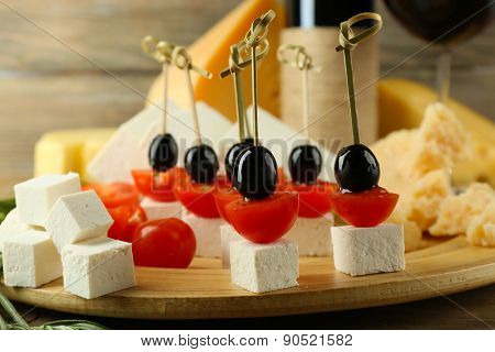 Cheese canapes with wine on table close up