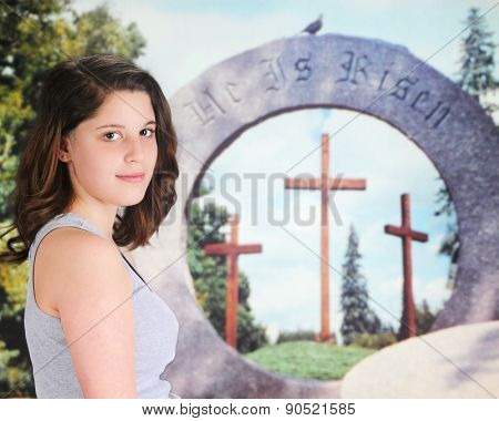 A beautiful teen girl looking back at the viewer as she stands near an outdoor Christian Easter display -- three crosses through the opening of a round hewn stone.