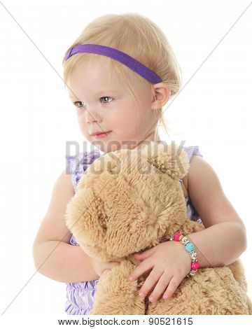 An adorable 2-year-old girl standing with her big Teddy bear.  On a white background.
