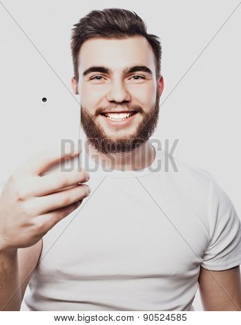 life style, happiness and people concept: young bearded man with mobile phone  in hand  against grey background.