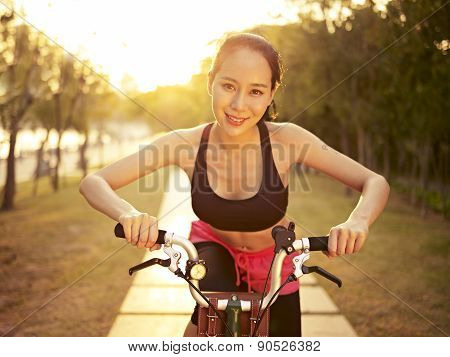 Young Asian Woman Riding Bike Outdoors At Sunset