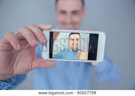 Smiling man showing thumb up and making selfie photo on smartphone