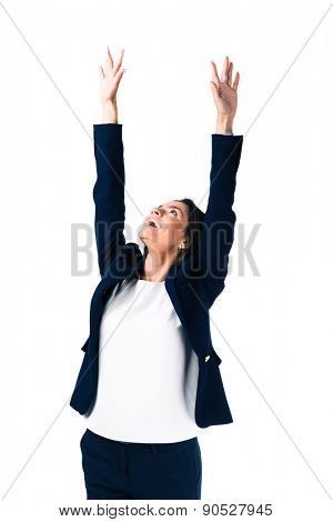 Portrait of a happy businesswoman with raised hands up standing over white background. Looking up