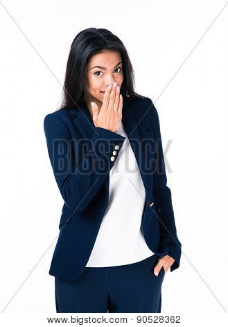 Beautiful businesswoman covering her mouth with hands and looking at camera. Isolated over white background
