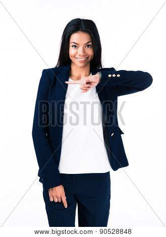 Smiling young businesswoman pointing finger away over white background and looking at camera