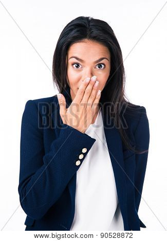 Young businesswoman covering her mouth over white background and looking at camera