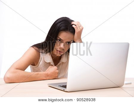 Angry woman sitting at the table with laptop over white background. Looking at laptop screen