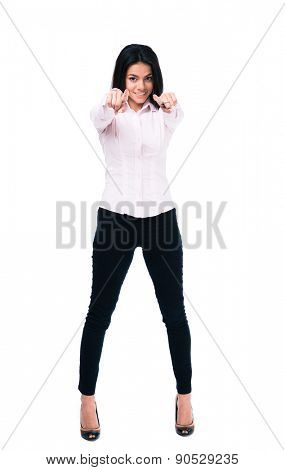 Full length portrait of a smiling businesswoman pointing at camera. Isolated on a white background