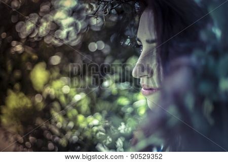 Teenager, melancholy young girl in a forest with sad gesture