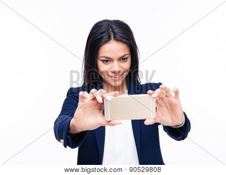 Happy businesswoman making photo on smartphone isolated on a white background