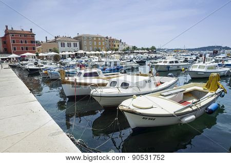 Moored Boats With City Promenade Of Rovinj In Background