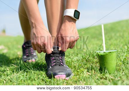 Running shoes, sports smartwatch and green smoothie. Female runner tying shoe laces in city park while drinking a healthy spinach and vegetable smoothie using smart watch heart rate monitor.