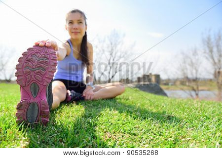 Fit fitness woman doing stretching exercises outdoors on grass. Girl doing hamstring leg stretching exercise and stretches. Female sports model exercising outdoor in summer. Beautiful Asian girl.