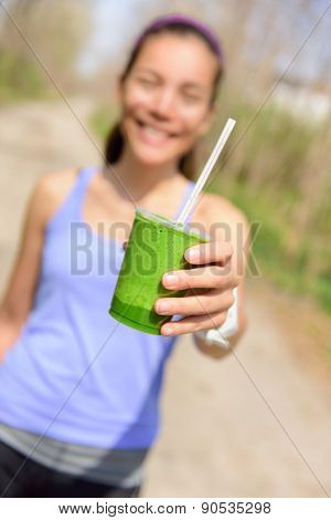 Green vegetable smoothie - healthy eating concept. Close up of green vegetable detox smoothie with spinach. Woman hand holding vegetable smoothies outdoors in forest.