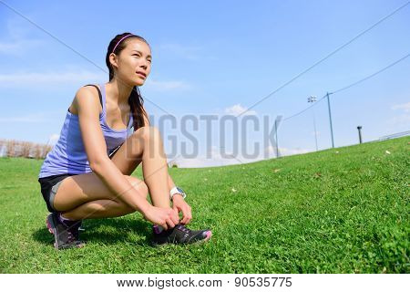 Young sporty woman runner preparing for run in morning in the beautiful nature. Wellness and healthy lifestyle concept with mixed race Asian Caucasian female model going running.