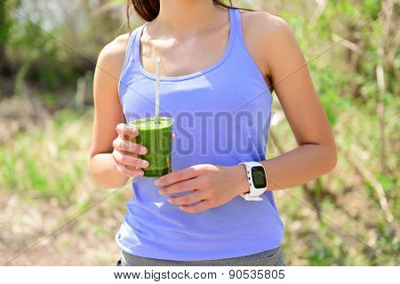 Green smoothie - woman runner wearing smartwatch. Healthy woman drinking vegetable smoothie wearing smart watch heart rate monitor during outdoor running workout in forest.