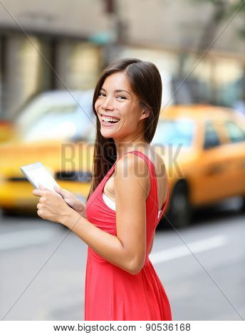 Woman in New York City using Tablet computer, standing in street with yellow taxi cab. Beautiful young woman in red dress smiling happy. Mixed race female model in Manhattan, New York City, USA.