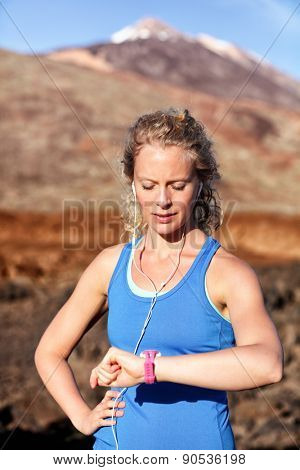 Runner looking at heart rate monitor sports smart watch after running with earphones listening to music. Female athlete checking pulse during workout run exercise outdoors in beautiful landscape.