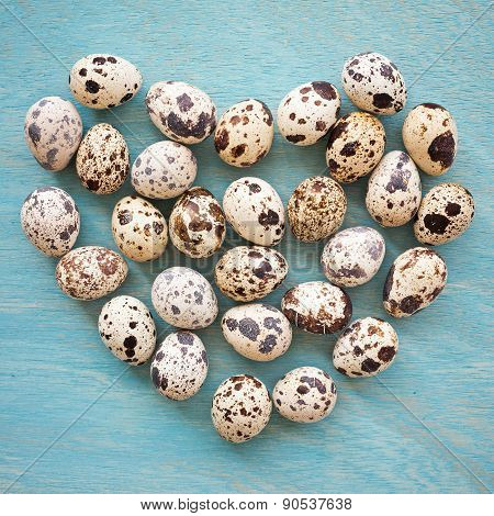Quail Eggs In Shape Of Heart On A Blue Wooden Background, Top View, Square Frame