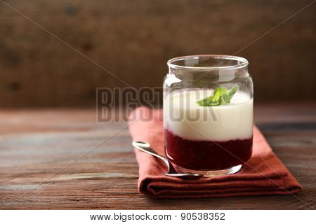 Glass jar with tasty panna cotta dessert on plate, on wooden table