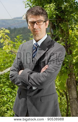 portrait of a young businessman thinking with glasses, outdoors