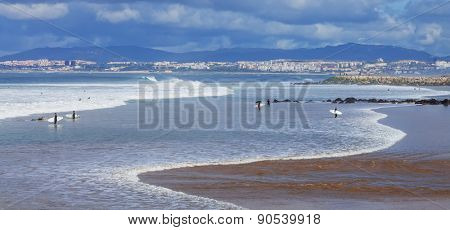 Costa da Caparica, Portugal. April 19, 2015: Surfers in the beach with Lisbon in background. This is an iconic location for surf in Portugal because its one of the pioneer beaches and quality of waves