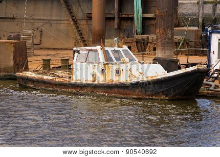 small rusty old ship lying next to the dock