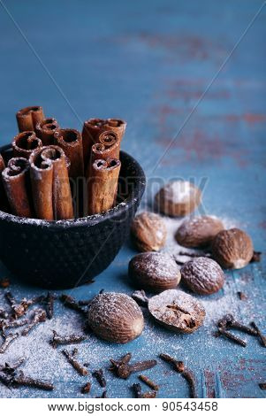 Cinnamon sticks in bowl, nutmeg and cloves on color wooden table background