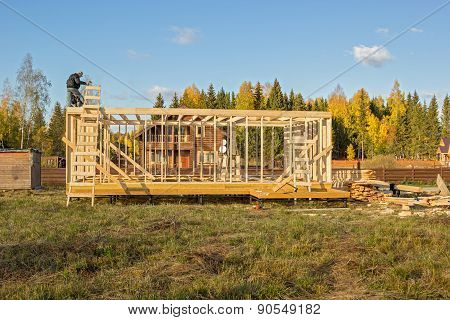 builders install a wooden frame of a house