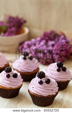 Cupcakes dessert decorated with berries in purple color and lilac on background. Natural light, rust