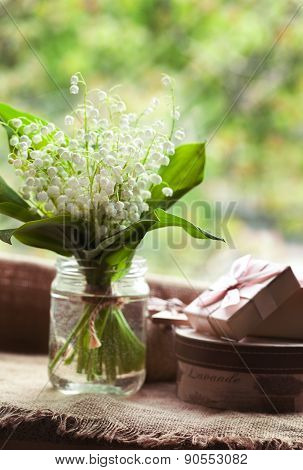 Blooming lily of the valley flowers  in glass with water on rustic textile background. Natural light