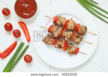 Traditional turkey kebab skewer barbecue meat with vegetables and sauce on white dish