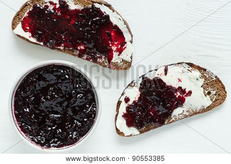 Heathy whole wheat toast with butter and jam on white kitchen table
