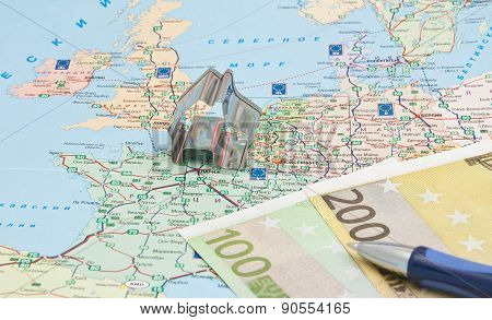 Pen, Money And House Model On Map