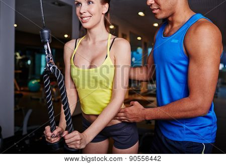 Trainer helping fit girl to exercise on facilities